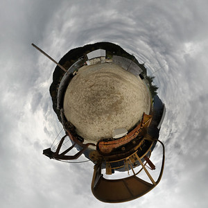 "A ""little planet"" panorama taken on Douglas Island Alaska near Juneau Alaska of a Bulldozer with logging trailer & a large log used for loggers to practice climbing trees at the 11 o'clock position.  Shot with a Nikon d700 on a Nodal Ninja Head, edited in PT GUI, Photoshop CS5 & Topaz Adjust."