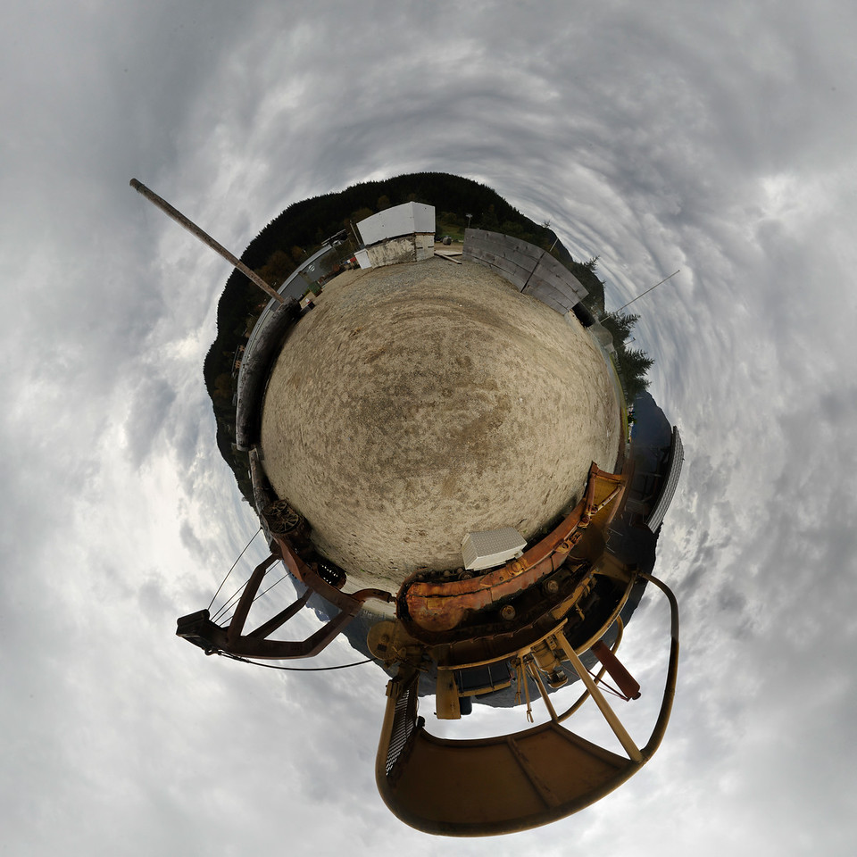 """A """"little planet"""" panorama taken on Douglas Island Alaska near Juneau Alaska of a Bulldozer with logging trailer & a large log used for loggers to practice climbing trees at the 11 o'clock position.  Shot with a Nikon d700 on a Nodal Ninja Head, edited in PT GUI, Photoshop CS5 & Topaz Adjust."""
