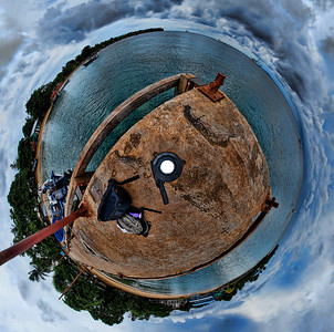 "Taken from the end of the Pier on Little Corn Island off the Nicaraguan Coast.  Taken with a Sony Alpha a300 on a Nodal Ninja Head, edited in PT GUI, Photoshop CS5 & Topaz Adjust, oriented in ""little planet"" view, creating the 360 degree sky."