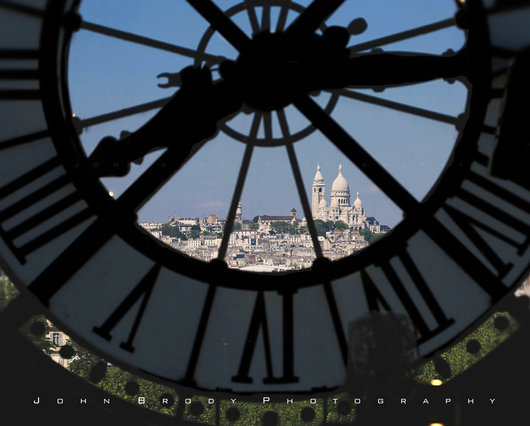 Sacre Coeurs and Montmartre hill shot through the d'Orsay Museum Clock