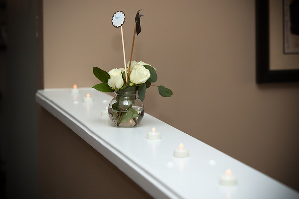 Flowers with electric votive candles on top of the entry half wall
