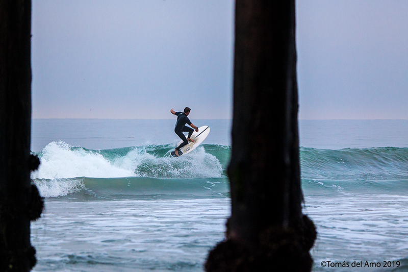 Surfer in the early morn from underneath Crystal Pier.