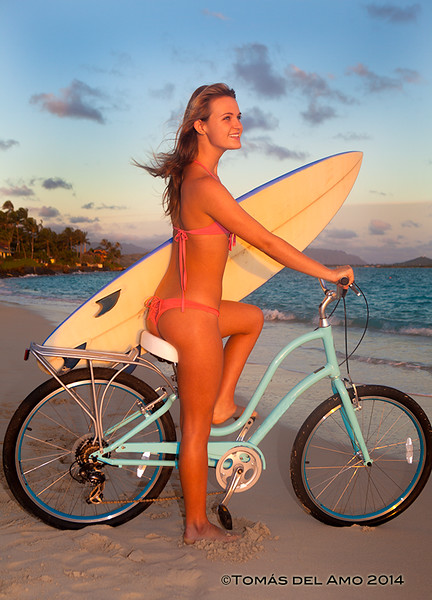 Teenage girl on her bike with surfboard checking out the waves.