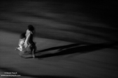 Man and child running in streets of Islamabad. It was pitch black due to night and loadshedding. They were out in street to escape the heat, i could hear the little kid giggle and enjoy the situation.
