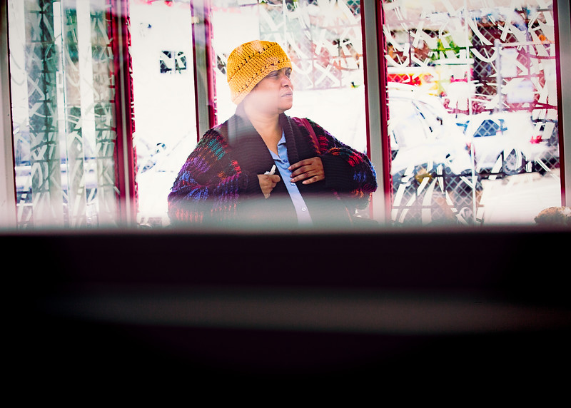 A woman in a colorful sweater and yellow-knitted cap waits for her bus on SW Alaska Street in West Seattle. Shot from inside bus #50 on the way to Seattle.
