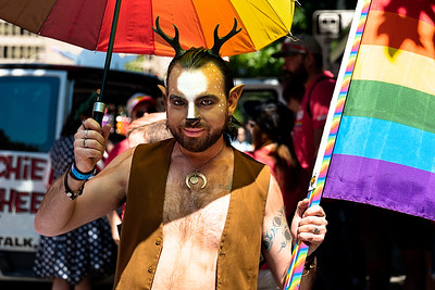 A 2019 Seattle Pride Parade participant, dressed as a horned goat, poses under an umbrella.