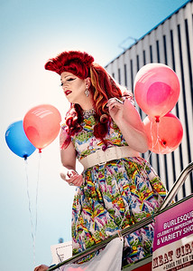 A Seattle Pride Parade participant, wearing a colorful unicorn dress, looks down below from the top deck of a sight-seeing bus.