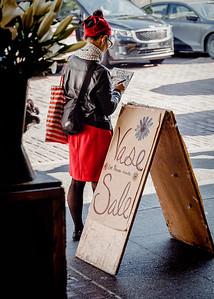 A young woman dressed in red sketches the Public Market Center in Seattle.
