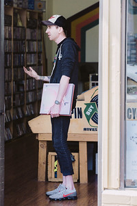 A young man with several LP's, including Purity Ring, gestures to the record store associate.