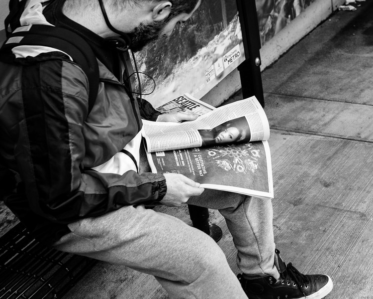 A man sitting at a bus stop looks through the Seattle Weekly with a young woman's face on the left side, which appears to be looking at me.