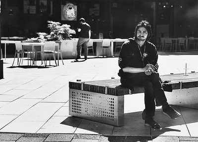 A man wit a peculiar expression on his face sits on a bench at a bus stop.