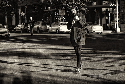 A man lights up a cigarette while crossing the street in the Junction, West Seattle