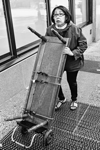 A woman uses a dolly to transport a coffee table in downtown Seattle