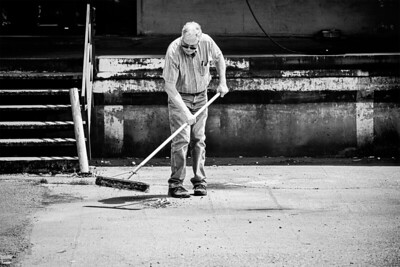 A  man with a large broom sweeps up debris in front of a loading dock along Occidental Ave S in Seattle.