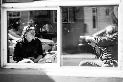 Window reflection of an older man taking a picture of the woman he's having coffee with at Firehouse Cafe in Fairhaven, WA.