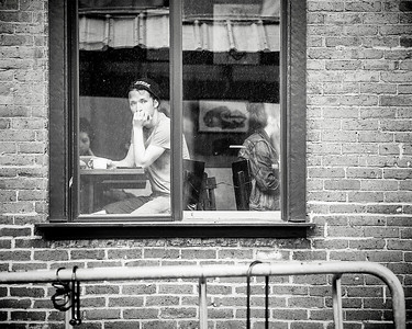 A young man inside a coffee shop stairs out a dirty window in Fairhaven, WA.