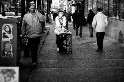 """A young woman pushes her suitcase - with a """"Fuck Em!"""" sticker plastered on it - along a downtown Seattle sidewalk."""