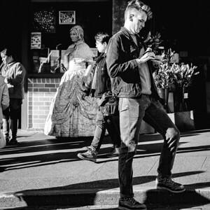A street photographer checks the settings on his camera.