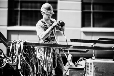 Construction worker handling hose on the back of a truck in Seattle.