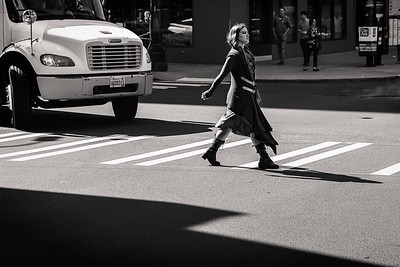 A young woman crosses the street in downtown Seattle.