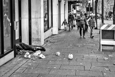 Passersby look over at a homeless, older man lying down who shakes from either the cold, alcohol or both. Aside from the takeout cartons strew all over, the stench from a big pile of feces and a urine soaked sidewalk was overwhelming.   Seattle, WA