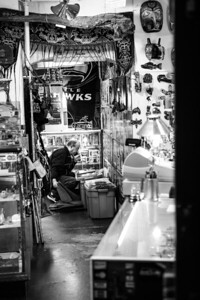 A man on his phone restocks products at a retail store in Pike Place Market, Seattle.
