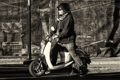 A bearded young man on a scooter stopped at a light in West Seattle
