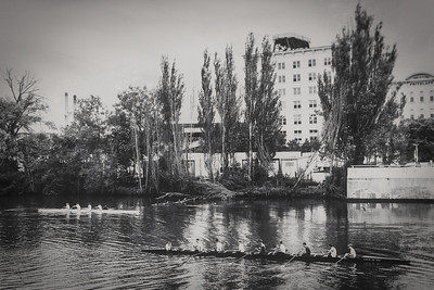 Girls and boys rowing in the Milwaukee River with the Fritzlaff building in the background.