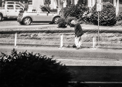 Window reflection of an older man stopping to kick curbside debris into a pile.