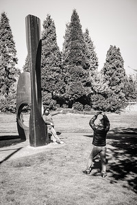 A woman poses for her partner at Seattle Center next to a metal sculpture.