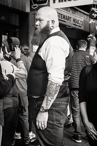 A man with a cool beard, earring, and arm tattoo at Pike Place Market.