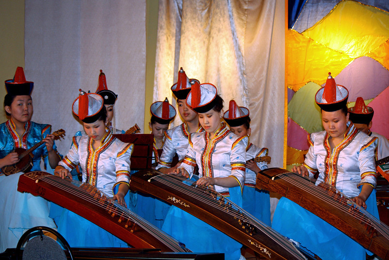 Buryat ladies playing the guzheng (Chinese name) or yatag (Mongolian name), an instrument related to the zither. (Aginskoye, Siberia)