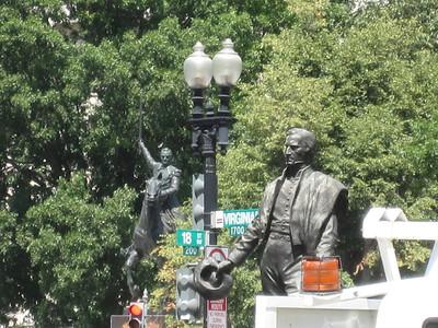 A line of four: amber light (10 feet), statue 1 (across a four-lane street), lamp post (40 feet beyond statue 1), statue 2 (100 feet away)
