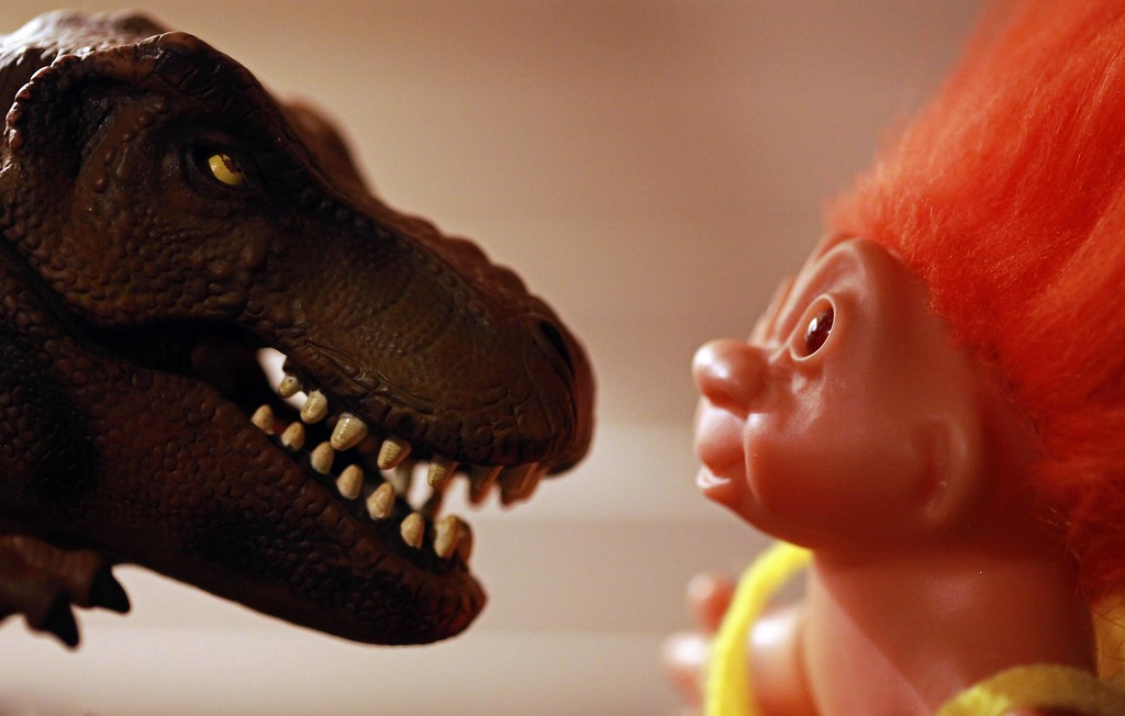 A fearsome T Rex catches the attention of a wide-eyed and fearful troll doll. A hair-raising experience! April 13. Oakland, CA.