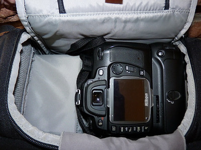 LowePro SlingShot 200 AW camera bag. Holds a ful sized DSLR with battery grip nicely, easily accessible.