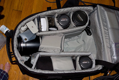 Lowepro Computrekker backpack.  It stores most of my gear, plus it has a laptop sleeve (closest to my back), which fits my MacBook Pro.  Demb Flash Diffuser is visible, AA Battery charger, ExpressCard CF reader, wireless flash trigger, tripod base, spare Canon batteries under, cable release.  Missing is the EF 24-70 f/2.8L and my Digital Rebel XTi.