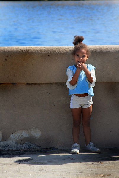 Girl in Havana, Cuba watching her father fish.
