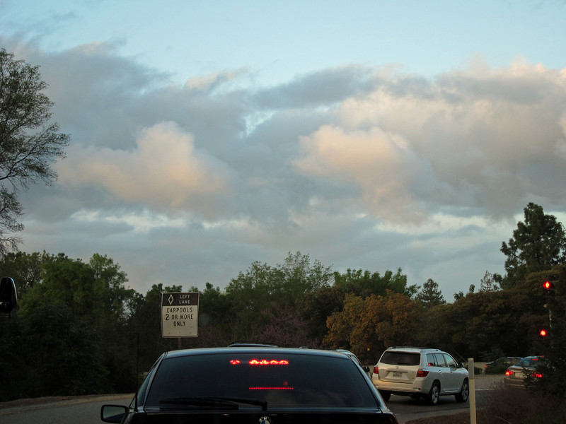 March 10. I was stopped at a metering light on a freeway on-ramp when the colors of the late afternoon clouds above the hard lights of the car and meter struck me. Very quick snapshot through the windshield.