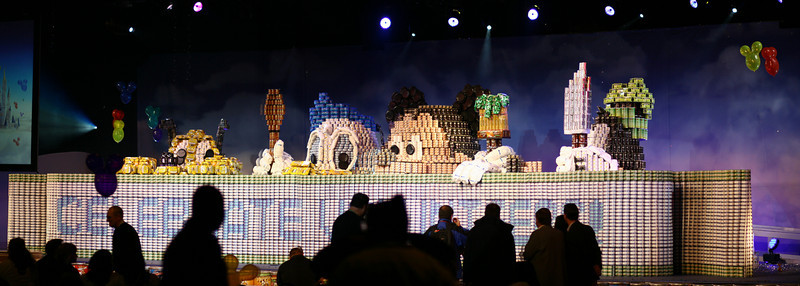 """February 17, 2010: Last week Epcot held a Press Event for """"Give a Day, Get a Disney Day""""! It was a ton of fun, but a VERY long day! Below is a photo of the world's largest structure made entirely out of cans (as certified by Guinness). There are well over 100,000 pieces of canned goods (beating the previous record of just over 46,000 pieces) in this structure! It was wall deCANstructed (and yes, it was CANstructed) and distributed to three food banks – in Orlando, Miami, and Atlanta."""