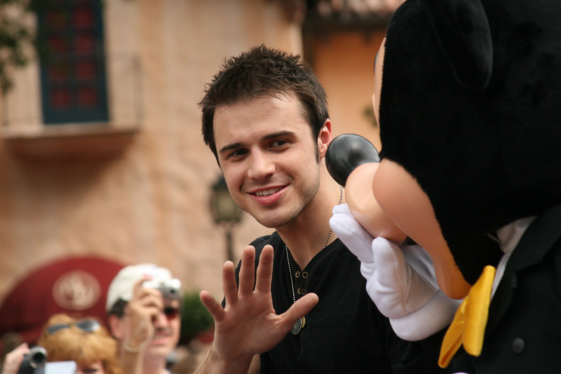 "June 1, 2009:  Another great weekend has come and passed.  Last week wasn't bad either, overall.  Today's photo is of Kris Allen, the current American Idol, on his motorcade parade at Disney's Hollywood Studios™ on Friday.  This really was a luck shot for me because a party of four was standing right in front of me and as Kris' car passed by they unfolded two HUGE banners.  I was able to snap this photo – along with one other – just as he passed.  Afterwards, he sang ""Heartless"" in front of the crowd.  For those of you familiar with this past season's American Idol, he is even better live than on the show.  So, Friday was a good day…also because I saw ""UP"".  GO AND SEE IT!"