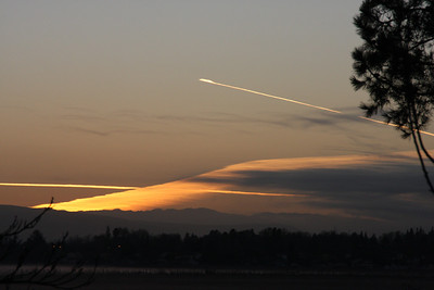 Jan 25: An unusual sunrise effect with the orange light gleaming off two jet trails and an oddly angled cloudbank over the mountains.