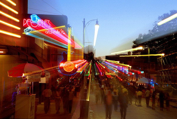 Crowds on Beale Street in Memphis, TN, are captured in a blur of neon lights at sunset.