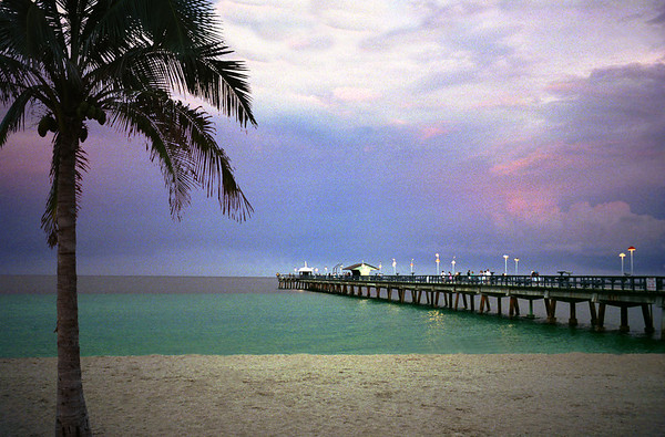 A beautiful blend of pastel colors surround the fishing pier as thunderstorms light up the evening sky near Lauderdale-by-the-sea, FL.