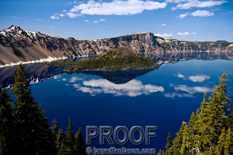 """The Deep Blue Reflection of Crater Lake""<br /> <br /> Crater Lake is the deepest lake in the United States at 1,900 feet deep.  Twenty-one square miles of intensely blue water awed me as I looked down from the cliff looming almost 2,000 feet above the shore.  The name ""Crater Lake"" is an anomaly as it was a volcano, not a meteor, that created this natural lake surrounded by steep walls of rock. Mount Mazama's eruption around 5,700 B.C. catapulted volcanic ash miles into the sky and expelled so much pumice and ash that the summit collapsed, creating a huge smoldering caldera which eventually filled with rain and snow melt.  Notice the stillness of the lake and how the reflection is actually a deeper blue then the sky."