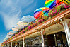 """Rainbow of Umbrellas - Pikes Place Market in Seattle""<br /> <br /> Strolling along Pikes Street in Seattle on a sunny warm afternoon I noticed the colorful umbrellas from outside this second floor cafe.  The umbrellas contrasted the sky seeming to create a rainbow appearance.  I used a wide angle lens to frame this shot."