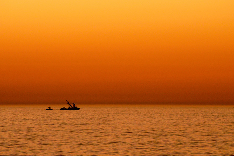 A small fishing boat heads back to the harbor as the sun sets on Monterey Bay.