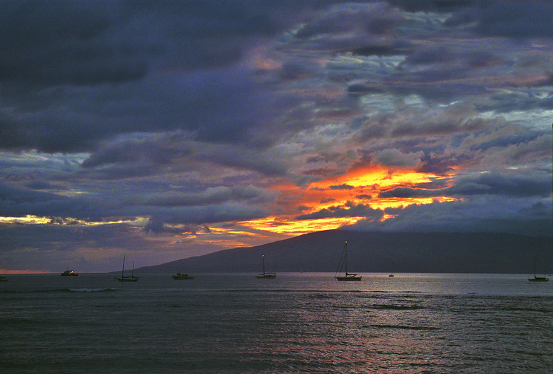 The sun sets on a small harbor in Maui, HI, as storm clouds gather.