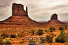 """The Mittens of Monument Valley""<br /> <br /> This photograph is the quintessential landscape of the Wild West.  Monument Valley, located in northern Arizona, is run by the Navajo Nation tribes.  To see Monument Valley requires a 17 mile round trip drive on a very rough dirt road.   We arrived under skies of thick gray clouds.  My patience paid off when finally the sun barely peaked through the clouds just long enough to get one of my favorite photos.  This photograph is actually a combination of three shots which together fully captured the high dynamic lighting seen in the final product."