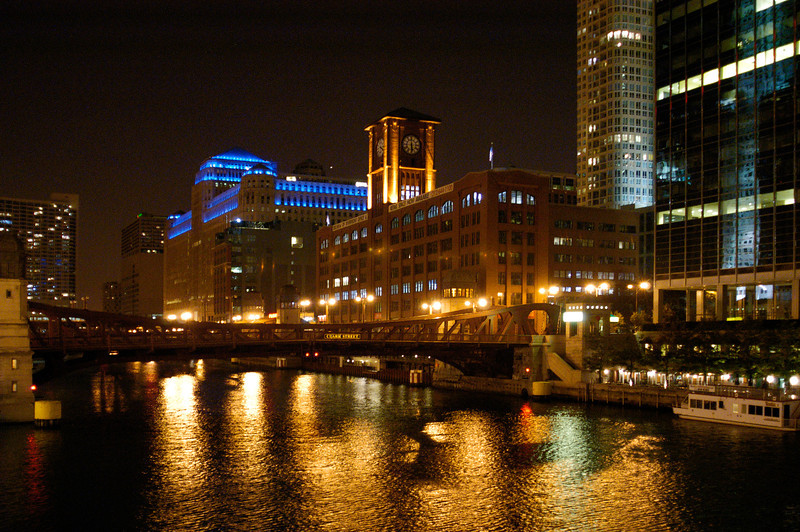 Night time view of downtown Chicago buildings reflected in the waters of the Chicago River.
