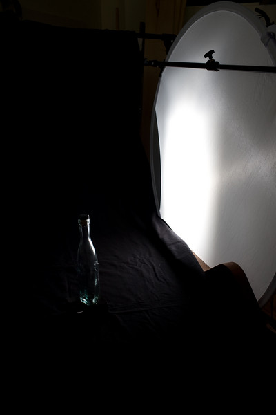 To create a visbile reflection on the bottle I have used a black back drop and placed my white diffuser to right of the bottle and slightly behind it. The flash, triggered by a Canon ST-E2 infared trigger and set to 1/8 power is on a stand behind the diffuser. I have adjusted the bottle and flash position so the reflection of the light is visible in the flat surface on the side of this triangular bottle.